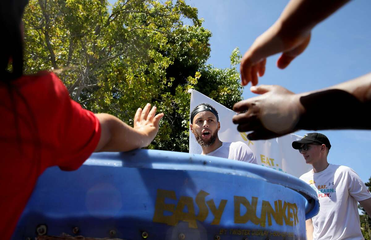 School children reach for Golden State Warriors guard Stephen Curry after he fell into a splash dunk tank during the launch of Eat, Play, Learn, at Lakeside Park at Lake Merritt in Oakland, Calif., on Thursday, July 18, 2019. Curry and his wife Ayesha started the new foundation that focuses on providing support for the 3 basic ingredients of a healthy childhood. They are partnering with Oakland Parks and Recs and other local entities to provide services for underserved Oakland children.