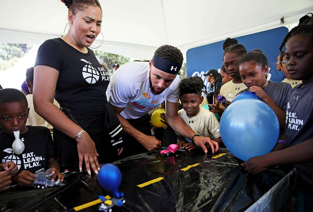 Ayesha Curry and her husband, Golden State Warriors guard Stephen Curry, watch a Lego car drive with a balloon as they interact with Davon Simmons (standing beside Stephen), 9, and Kess'ya John (second from right), 9, during the launch of Eat, Play, Learn, at Lakeside Park at Lake Merritt in Oakland, Calif., on Thursday, July 18, 2019. The Bay Area couple started the new foundation that focuses on providing support for the 3 basic ingredients of a healthy childhood. They are partnering with Oakland Parks and Recs and other local entities to provide services for underserved Oakland children.