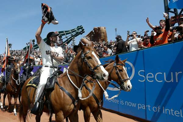San Francisco Giants pitcher Madison Bumgarner carries the 2014 Giants championship pennant while riding a San Francisco Police horse in the AT&T Park outfield before a baseball game between the Giants and the Colorado Rockies in San Francisco, Monday, April 13, 2015. (AP Photo/Jeff Chiu, Pool)
