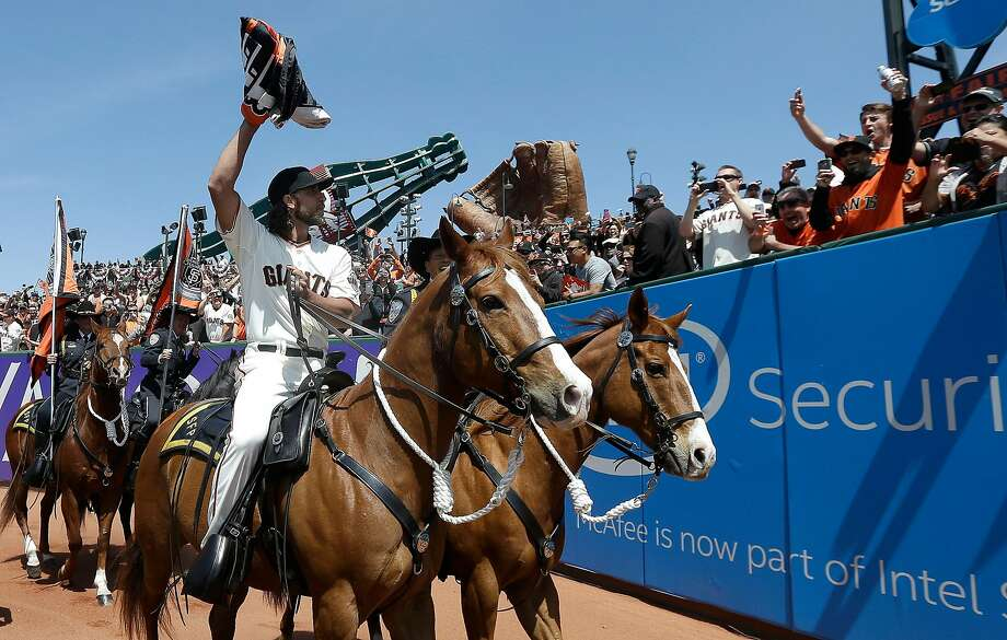 San Francisco Giants pitcher Madison Bumgarner carries the 2014 Giants championship pennant while riding a San Francisco Police horse in the AT&T Park outfield before a baseball game between the Giants and the Colorado Rockies in San Francisco, Monday, April 13, 2015. (AP Photo/Jeff Chiu, Pool) Photo: Jeff Chiu / Associated Press