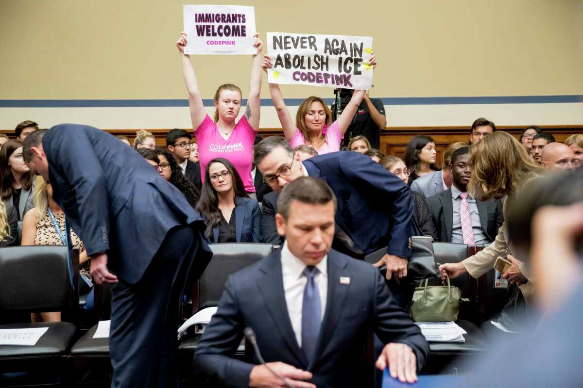 Activists with Code Pink hold up signs that read