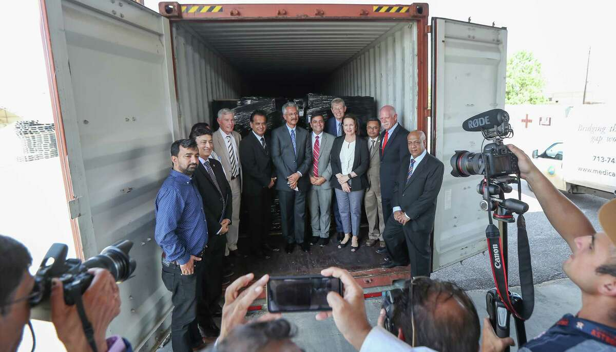 The Houston nonprofit Medical Bridges, Helping Hands and dignitaries cut a ceremonial ribbon in front of a shipping container with hospital beds and 12 pallets of medical supplies to Pakistan Thursday, July 18, 2019, in Houston.