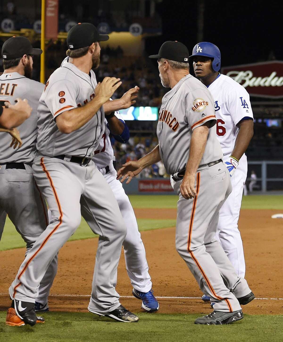 San Francisco Giants starting pitcher Madison Bumgarner, second from left, and Los Angeles Dodgers' Yasiel Puig, right, argue as first base coach Bill Hayes stands between them during a scuffle that emptied both benches after Puig was thrown out at first by Bumgarner during the seventh inning of a baseball game, Monday, Sept. 19, 2016, in Los Angeles. (AP Photo/Mark J. Terrill)