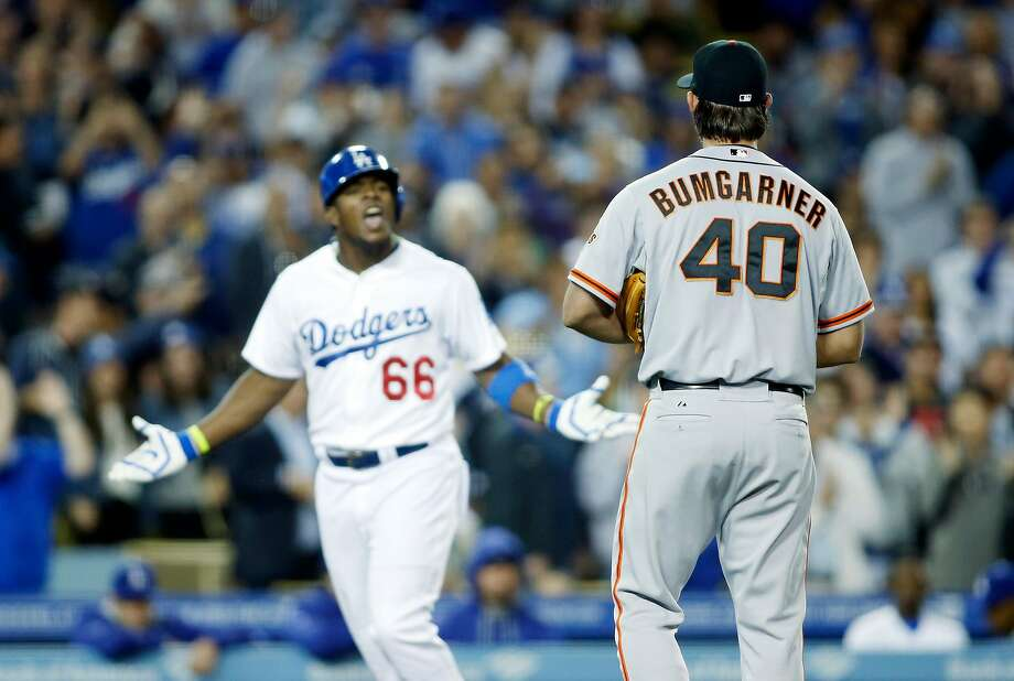 San Francisco Giants starting pitcher Madison Bumgarner, right, and Los Angeles Dodgers' Yasiel Puig, left, exchange words as Puig runs down the third base line after hitting a solo home run during the sixth inning of a baseball game, Friday, May 9, 2014, in Los Angeles. (AP Photo/Danny Moloshok) Photo: Danny Moloshok, AP