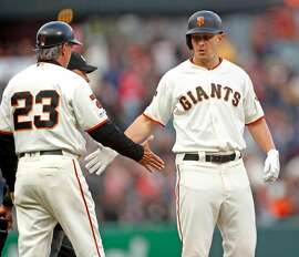 San Francisco Giants' Alex Dickerson slaps hands with Ron Lotus after tripling in 2nd inning against New York Mets during MLB game at Oracle Park in San Francisco, Calif., on Thursday, July 18, 2019.