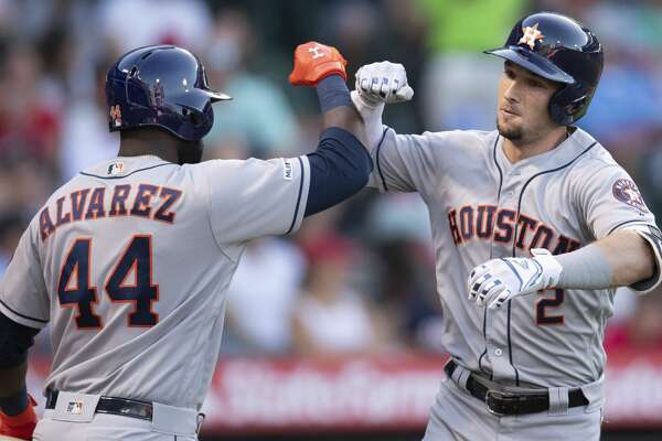 Houston Astros' Alex Bregman, right, celebrates his solo home run with Yordan Alvarez during the fifth inning of the team's baseball game against the Los Angeles Angels in Anaheim, Calif., Thursday, July 18, 2019. (AP Photo/Kyusung Gong)