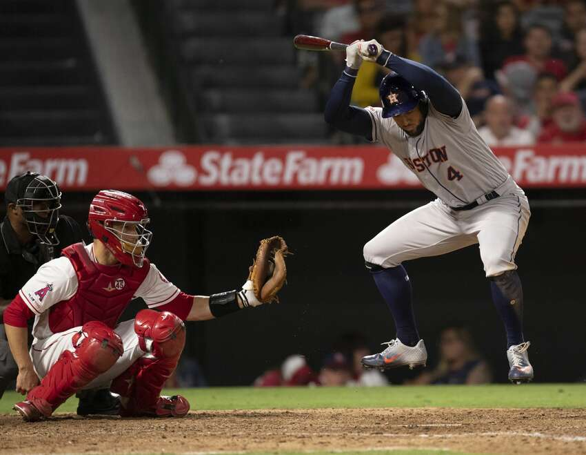 Houston Astros' George Springer, right, leaps to evade an inside pitch during the ninth inning of the team's baseball game against the Los Angeles Angels in Anaheim, Calif., Thursday, July 18, 2019. (AP Photo/Kyusung Gong)