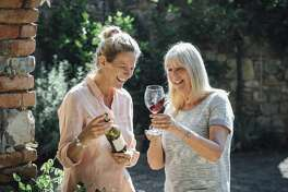 Two mature women discussing a bottle of red wine on their holiday. They are standing in the garden of their Villa.