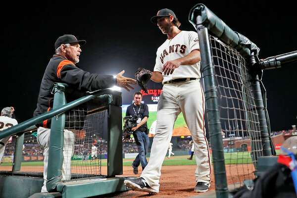 San Francisco Giants' Madison Bumgarner is welcomed back to the dugout by manager Bruce Bochy after retiring the New York Mets in the 9th inning during MLB game at Oracle Park in San Francisco, Calif., on Thursday, July 18, 2019.