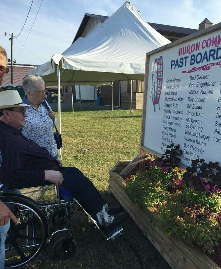 Warren and Grace Krohn are pictured at the 2018 Huron Community Fair, looking at the sign listing past Huron Community Fair Board Members. (Courtesy Photo)