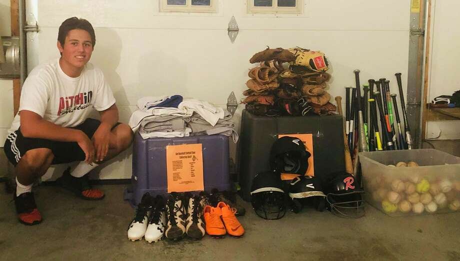 Ridgefield High School senior Will Carbonari with the baseball equipment he collected this summer. Photo: Ron Feuchs / Contributed Photo