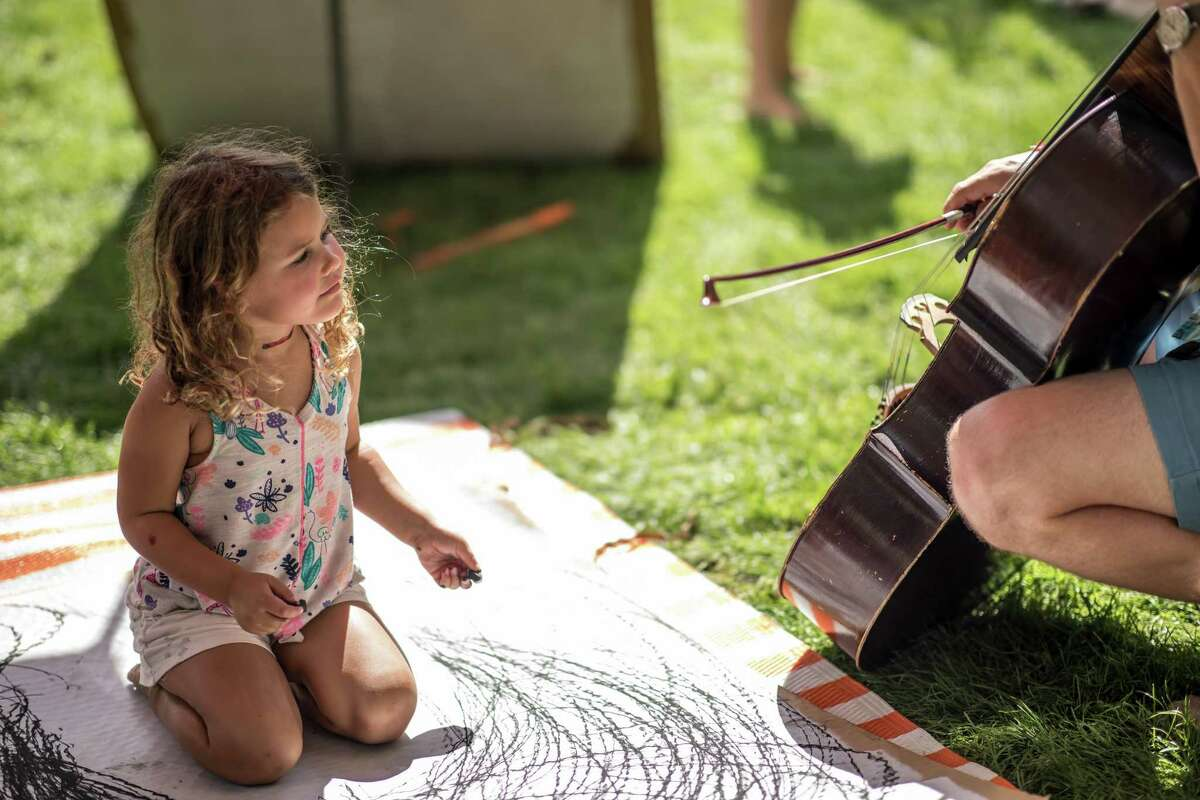 A child gets a closeup view of a cello at last year's Five Senses Festival.