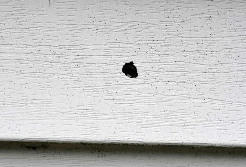 A bullet hole is visible in the rear of a Third Avenue home where a 3-year-old boy was shot in the arm with a stray bullet fired during a shootout on Friday, July 19, 2019, in Albany, N.Y. (Will Waldron/Times Union)