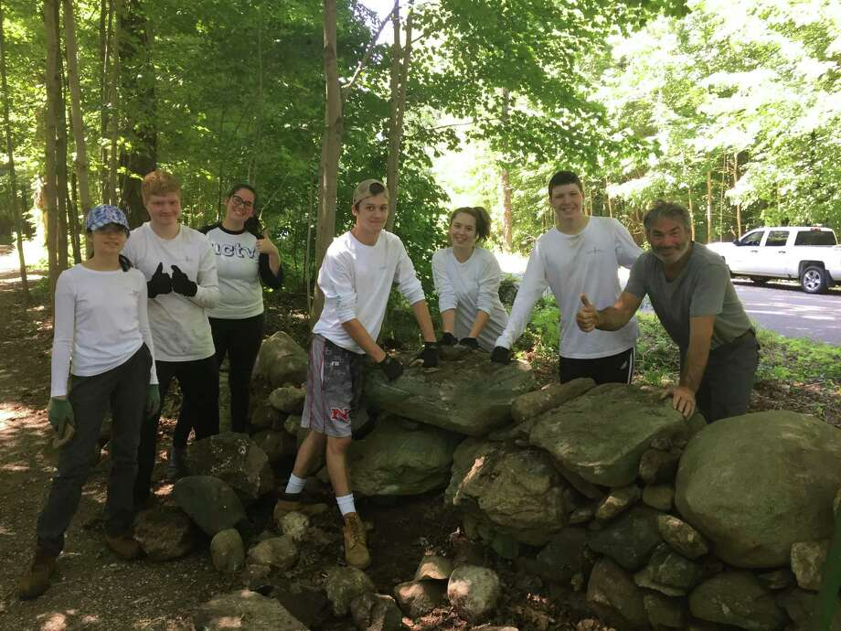 Waveny Park Conservancy Summer Stewards reset the Lapham Road stone wall at Waveny Park, guided by Master Stonemason Greg Faillaci. The restored wall with large capstones has generated many compliments from Waveny Park walkers and joggers. The Stewardship Program runs in conjunction with the New Canaan Land Trust and provides natural, outdoor experiences for local high school students. From left are Alexandra Schauer, Ben Walter, Kelly Flannery - Summer Programme Manager, Jake Harasiuk, Vivi Reeves, Alex Hazlin and Stonemason Greg Faillaci. Photo: Contributed Photo / Chris Schipper / New Canaan Advertiser Contributed