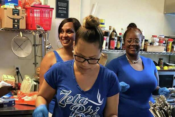 During their quarterly visit to the Gillespie Center in Westport on July 13, Waleska Macklin of Zeta Phi Beta's Norwalk chapter dishes up potato salad as Zeta Greta B. James (back, left) and volunteer Catherine Brown (back, right) look on.