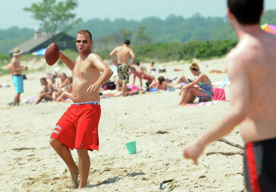Bogdan Nedelcu of Rocky Hill, left, tosses the ball with Kyle Fiengo of Meriden at Hammonasset Beach State Park, Madison, West Beach. Both are recent college grads. Mara Lavitt/New Haven Register mlavitt@newhavenregister.com 5/30/13