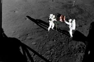 The deployment of the flag of the United States on the surface of the moon is captured on film during the first Apollo 11 lunar landing mission. Mission commander Neil A. Armstrong, standing on the left at the flag's staff, is pictured with astronaut Edwin E. Aldrin Jr. The picture was taken by a camera mounted in the lunar module.