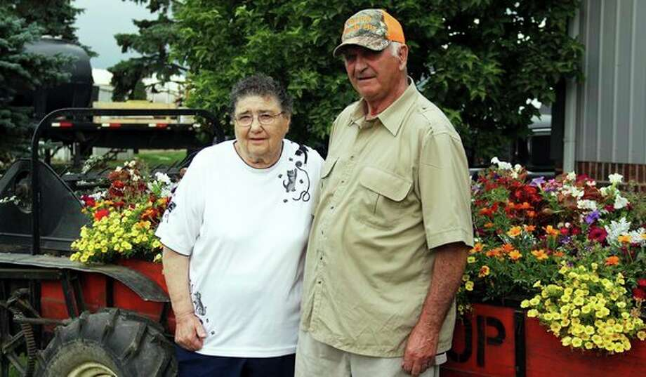 Janet and Melvin Bischer pose in front of Melvin's flower-filled manure spreader. They have been named 2019 Friends of the Huron Community Fair. (Andrew Mullin/Huron Daily Tribune)