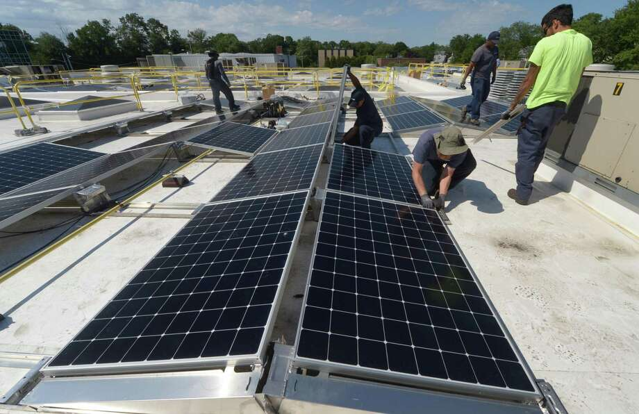 ENCON employees install solar panels on the roof of the Paul Miller Nissan dealership in Fairfield, which has installed the solar-energy array with financing from Darien-based Greenworks Lending, Wednesday, July 18, 2018, in Fairfield, Conn. Norwalk property owners could see a tax benefit if an ordinance goes through. Photo: Erik Trautmann / Hearst Connecticut Media / Norwalk Hour