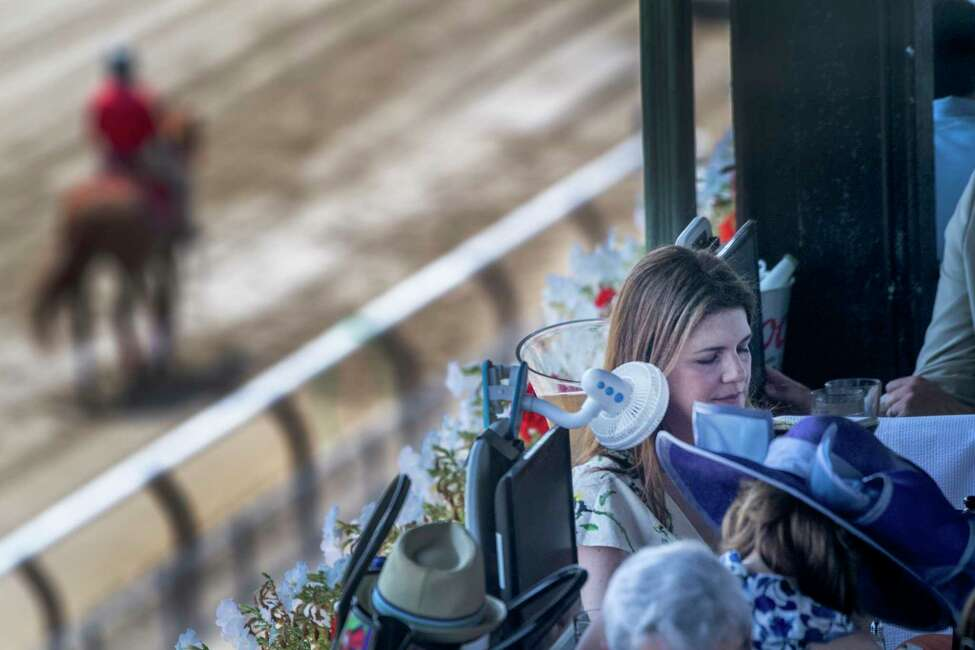 Race fan Nicole Loewenstern uses a fan to keep cool in the dining area at the Saratoga Race Course Friday July 20, 2019 in Saratoga Springs, N.Y. Special to the Times Union by Skip Dickstein