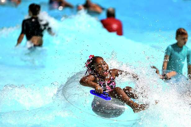 Destinee Lucas, 6, of Aliquippa, Pa., rides a wave at the pool at Settlers Cabin Park, Thursday, July 18, 2019, in Robinson, Pa. Communities nationwide are bracing for a record-breaking heatwave that's already roasting much of the U.S. to continue through the weekend. (Alexandra Wimley/Pittsburgh Post-Gazette via AP)