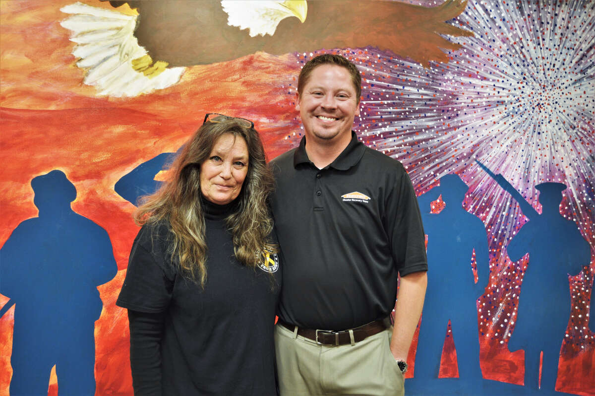 Debi Bartley-Ullom and Shawn Weiss pose for a photo on July 18, in front of the mural inside Aaron's Gifts From Home, located inside the Midland Mall. (Ashley Schafer/ashley.schafer@hearstnp.com)