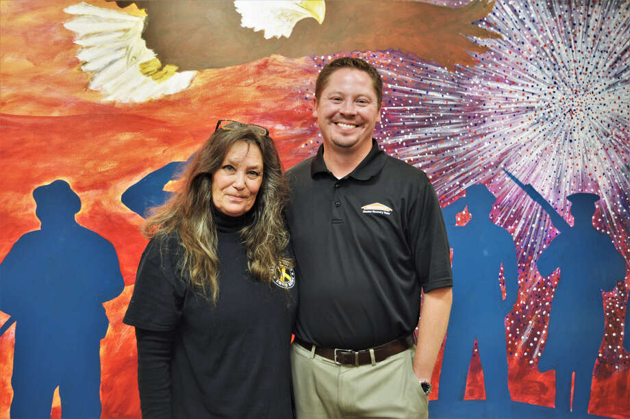 Debi Bartley-Ullom and Shawn Weiss pose for a photo on July 18, in front of the mural inside Aaron's Gifts From Home, located inside the Midland Mall. (Ashley Schafer/ashley.schafer@hearstnp.com) Photo: Ashley Schafer