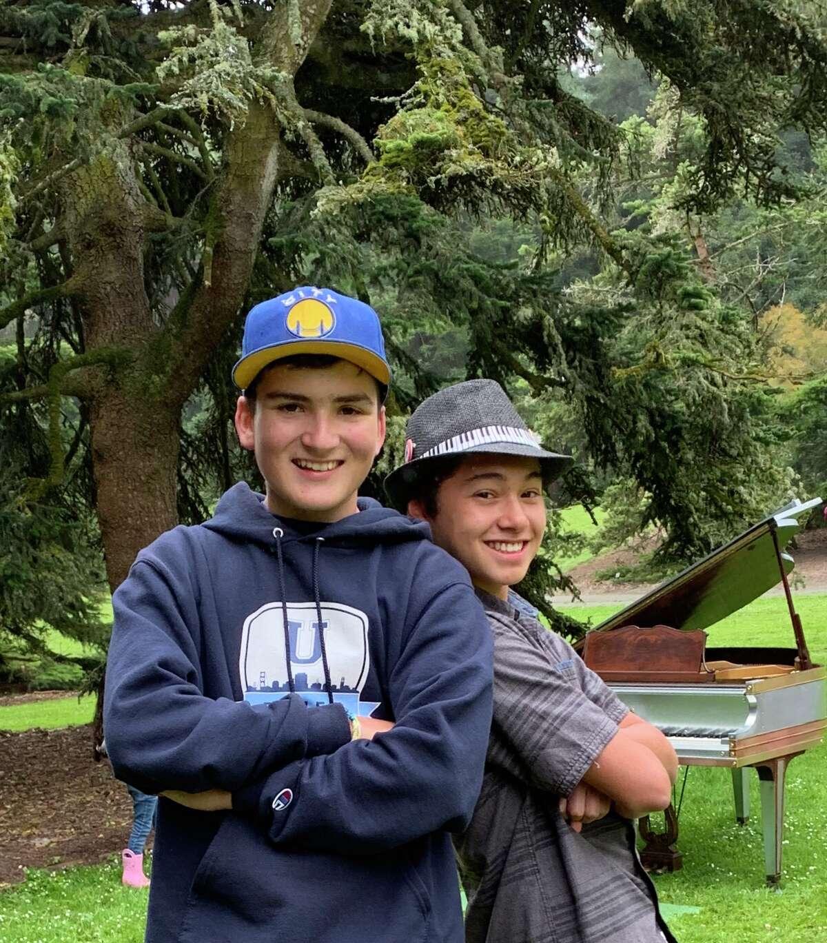 Oscar Cervarich, left, and Gavin Bermudez pose for a photo together near the pianos at the San Francisco Botanical Garden.