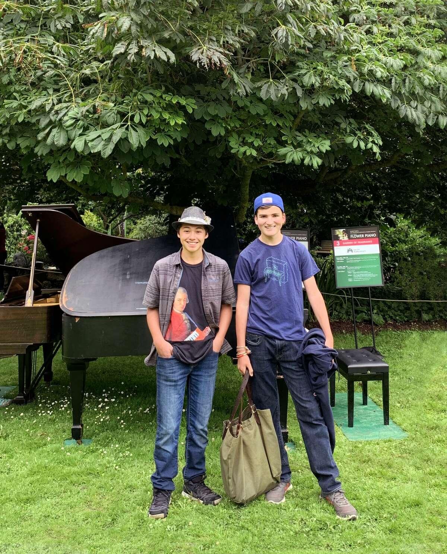 Gavin Bermudez, left, and Oscar Cervarich pose for a photo together near the pianos at the San Francisco Botanical Garden.