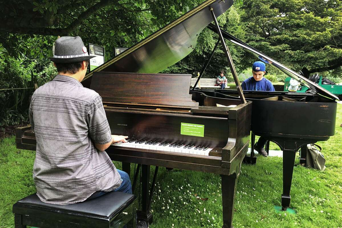 Gavin Bermudez, left, and Oscar Cervarich play the piano at Flower Piano at the San Francisco Botanical Garden.