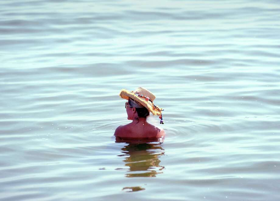 A woman wears a hat while she sits in Long Island Sound at Greenwich Point, Conn., Tuesday, August 28, 2018. Photo: File. / Hearst Connecticut Media / Greenwich Time