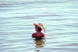 A woman wears a hat while she sits in Long Island Sound at Greenwich Point, Conn., Tuesday, August 28, 2018.