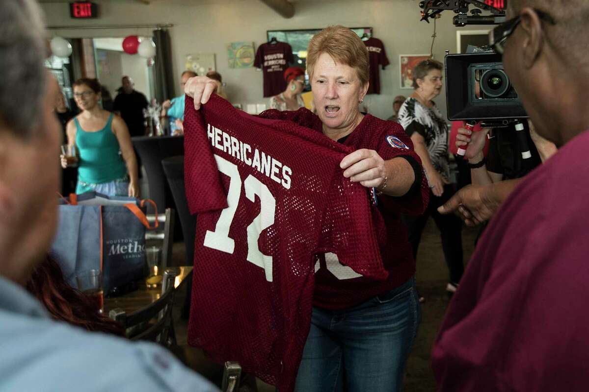 Billie Cooper lifts up a Houston Herricanes jersey during a reunion of Herricanes, the city's first professional women's football team, on Saturday, July 13, 2019, in Houston. The reunion marked the first time in 40 years the women who played in the NWFL gathered to relive the memories of their playing days.