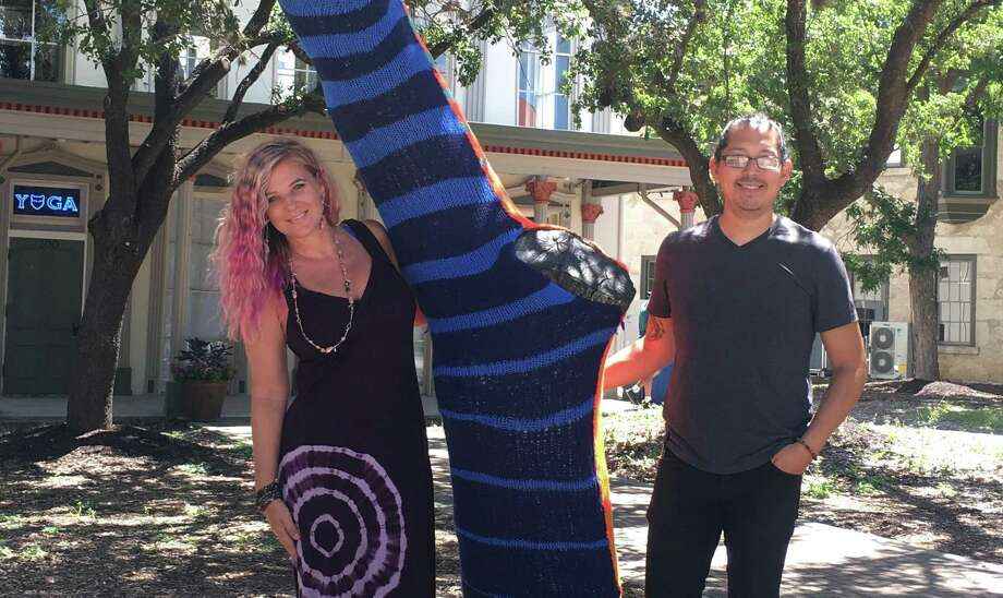 Billy Munoz, right, is working on a project to yarn bomb trees in Hemisfair. His first is outside Blue Cat Yoga and Healing Arts, which is owned by Trina Johansen, left. Photo: Crystal Henry