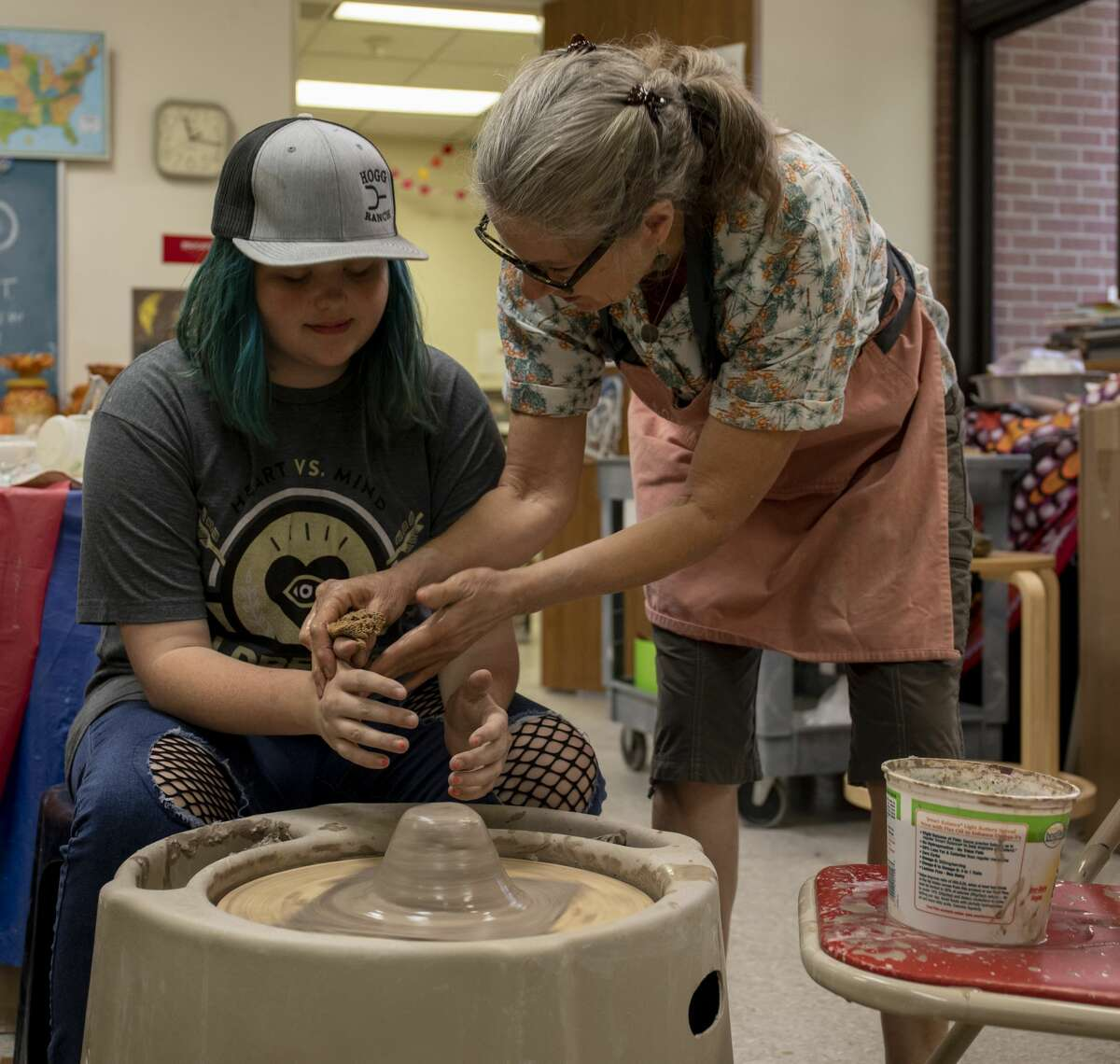 Teacher Karen Hembree shows Madison Moreland how to push the clay while throwing on the wheel during Teen Ceramics on Thursday, July 11, 2019 at the Ellen Noel Art Museum.