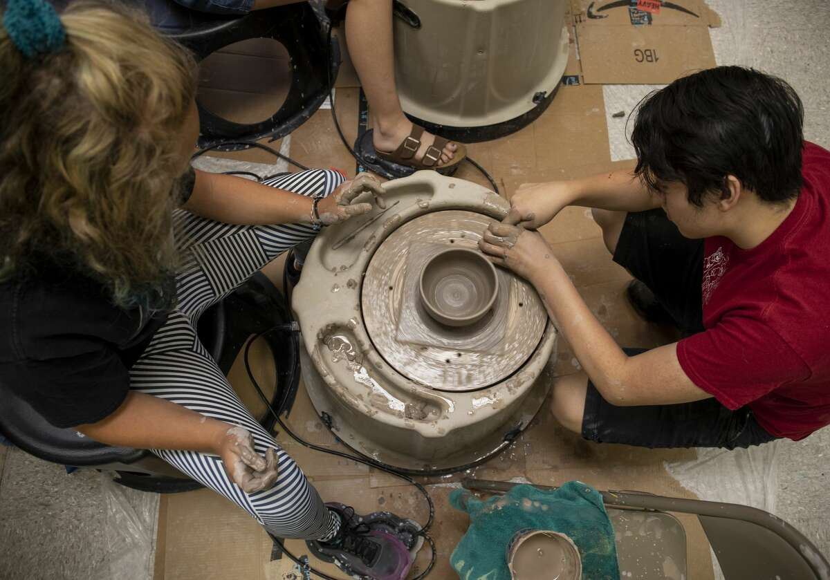 Teaching assistant Anil Asakawa shows Emma Craig how to get her bowl off the throwing wheel Thursday, July 11, 2019 at the Ellen Noel Art Museum.