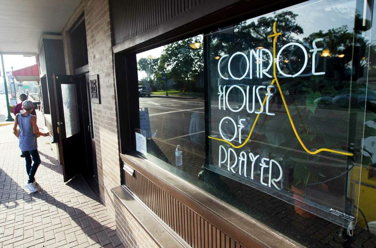"""A sign for Conroe House of Prayer is seen along West Davis Street, Wednesday, July 17, 2019, in Conroe. The Compassions United ministry group is in the process of developing five acres of land off Foster Drive donated to them by the city of Conroe. In addition to moving CHOP from its downtown location to the donated land, the organization hopes to develop a master planned community called """"Miracle City"""" to support people transitioning out of homelessness and to provide long-term supportive housing options for those requiring financial, emotional, and community support for an extended period."""