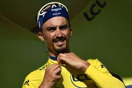 France's Julian Alaphilippe celebrates his overall leader's yellow jersey on the podium of the thirteenth stage of the 106th edition of the Tour de France cycling race, a 27,2-kilometer individual time-trial in Pau, on July 19, 2019. (Photo by Anne-Christine POUJOULAT / AFP)ANNE-CHRISTINE POUJOULAT/AFP/Getty Images