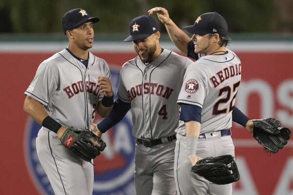 Houston Astros left fielder Michael Brantley, center fielder George Springer, and right fielder Josh Reddick, from left, celebrate the team's 6-2 win over the Los Angeles Angels in a baseball game in Anaheim, Calif., Thursday, July 18, 2019. (AP Photo/Kyusung Gong)