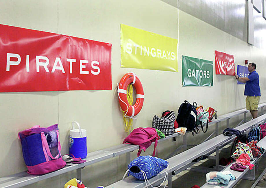 A volunteer worker places signs naming all five member teams of the Southwestern Illinois Swim Association on a wall of the pool deck at the Chuck Fruit Aquatic Center Friday evening in Edwardsville. The annual SWISA Swim Championship meet will be held there Sunday, the first time the end-of-year meet will be held indoors. Photo: Pete Hayes | The Telegraph