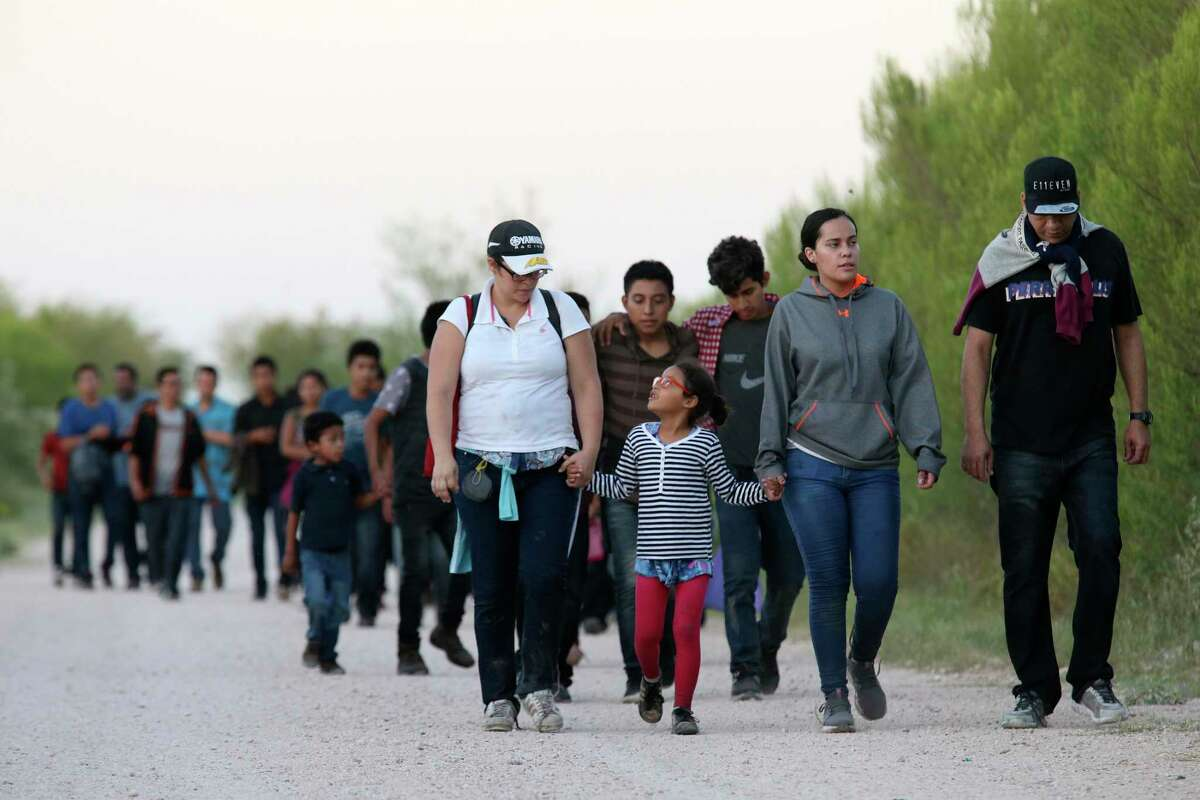 After crossing the Rio Grande, migrants walk near the Anzalduas International Bridge in Hidalgo County in July. As the Trump administration limits the number of refugees allowed to enter the United States, a reader reflects on how her family was welcomed here.