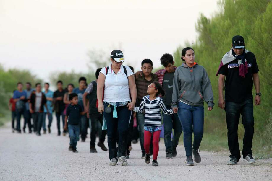 After crossing the Rio Grande, migrants walk near the Anzalduas International Bridge in Hidalgo County in July.  As the Trump administration limits the number of refugees allowed to enter the United States, a reader reflects on how her family was welcomed here. Photo: Jerry Lara /Staff Photographer / © 2019 San Antonio Express-News