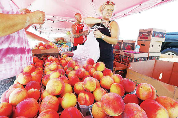 Krystal Rapp waits on customers at the fresh fruit stand Thursday across from the Phillips 66 gas station in West Alton, Missouri, where Calhoun County peaches were a popular item.