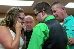 Monica Berckenhoff listens to her son's heart beat through Travis Stufflebean during the Berckenhoff wedding ceremony Friday, July 19, 2019 at the Montgomery County Justice of the Peace Precinct 1 courtroom in Willis. Stufflebean was given Colton Berckenhoff's heart after he died around seven years ago.