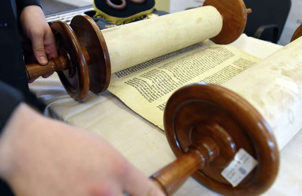 Rabbi Mordechai Rubin unrolls a 100-year-old Torah on Wednesday, June 26, 2019 at the Crossings Park in Albany, NY. (Phoebe Sheehan/Times Union)