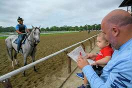 Thirteen month old Jordan Farrell does some race picking during breakfast at the track while in the arms of his father, Patrick Farrell formerly of Albany now living in Past Christian, Miss at the Saratoga Race Course Friday July 20, 2019 in Saratoga Springs, N.Y. Special to the Times Union by Skip Dickstein