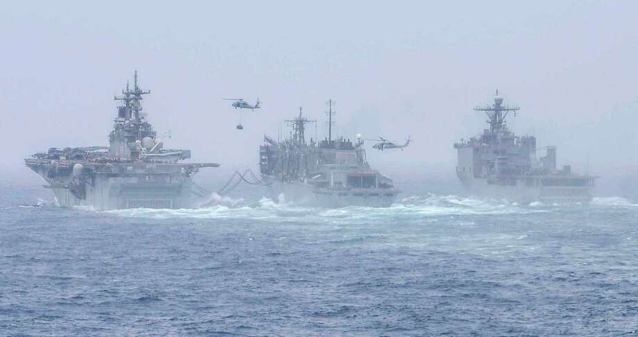 The amphibious assault ship USS Boxer, left, and the USS Harpers Ferry, far right, conduct a replenishment-at-sea with fast combat support ship USNS Arctic. They are deployed to the U.S. 5th Fleet area of operation. Photo: U.S. Navy Photo By Mass Communication Specialist 2nd Class Curtis D. Spencer / Public Domain