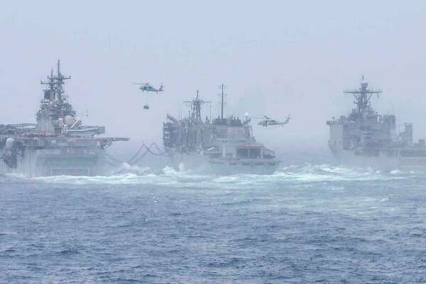 The amphibious assault ship USS Boxer, left, and the USS Harpers Ferry, far right, conduct a replenishment-at-sea with fast combat support ship USNS Arctic. They are deployed to the U.S. 5th Fleet area of operation.