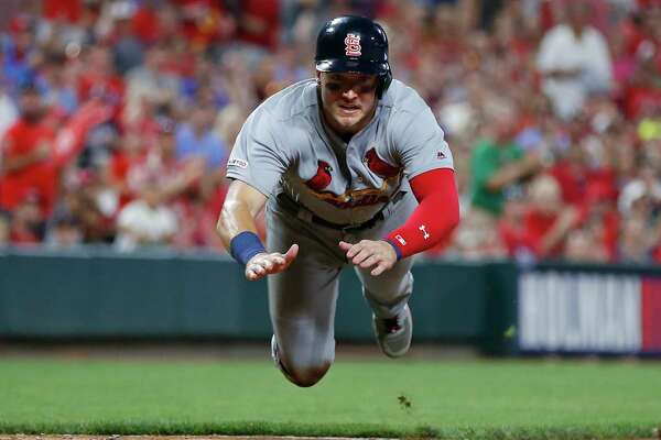 St. Louis Cardinals' Andrew Knizner, left, slides head first to score during the sixth inning of the team's baseball game against the Cincinnati Reds on Friday, July 19, 2019, in Cincinnati. (AP Photo/Gary Landers)