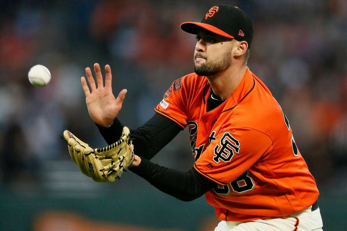 San Francisco Giants starting pitcher Tyler Beede (38) gloves the grounder and throws to first to force out New York Mets Adeiny Hechavarria (11) in the fifth inning of an MLB game at Oracle Park, Friday, July 19, 2019, in San Francisco, Calif.
